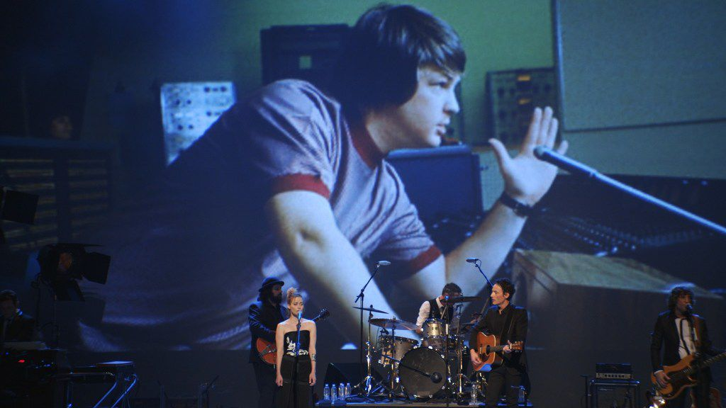 Songs are performed during Echo in the Canyon against a backdrop of a photograph of Brian Wilson of the Beach Boys.