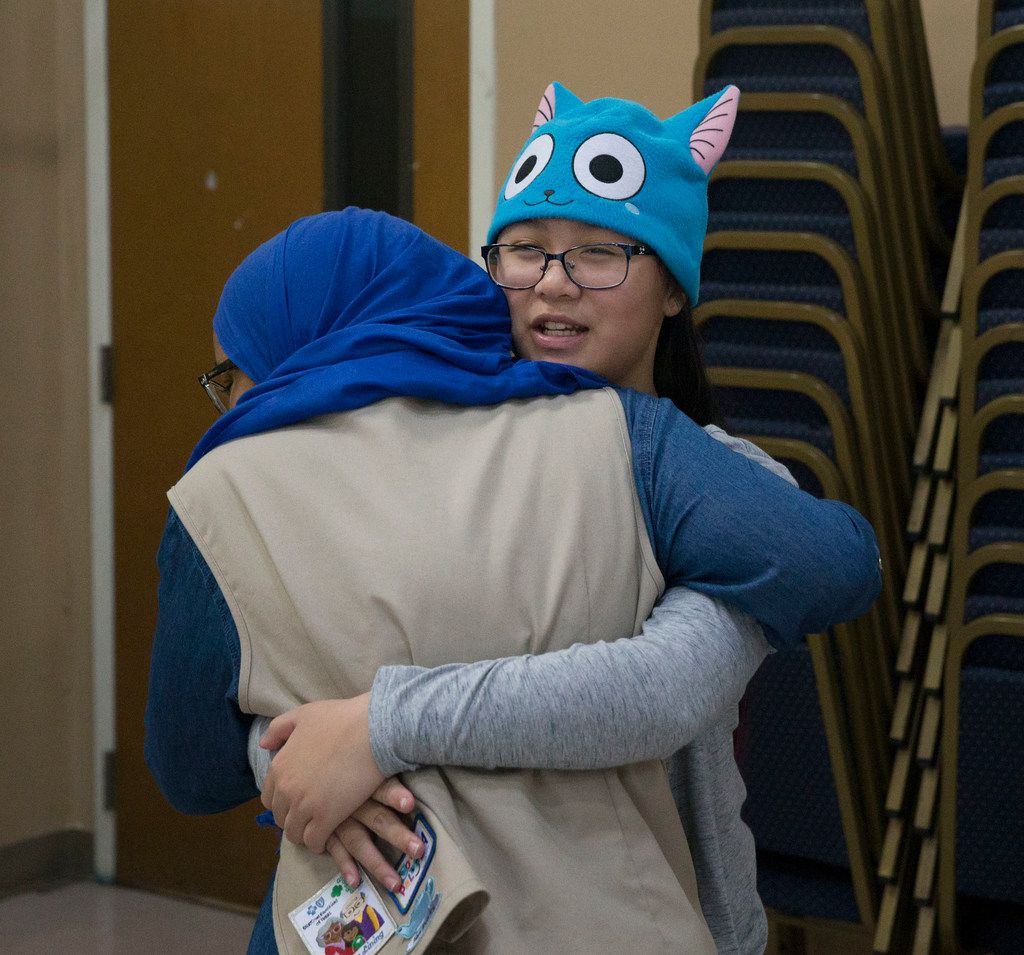 Girl Scout Cadettes Sophia Laska (right) of Troop 882, and Redda Hassen, Troop 647, hug before their combined meeting at the Islamic Association of North Texas mosque in Richardson. They were former classmates who were reunited at the meeting.