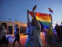 Michael Smith, 27, of Dallas, claps his hands while raising a gay pride flag during QueerBomb Dallas' march on June 29, 2014.