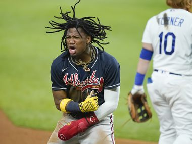 Atlanta Braves right fielder Ronald Acuna Jr. celebrates after advancing from first to third on a single by first baseman Freddie Freeman past the tag from Los Angeles Dodgers third baseman Justin Turner during the during the fifth inning in Game 2 of a National League Championship Series at Globe Life Field on Tuesday, Oct. 13, 2020.