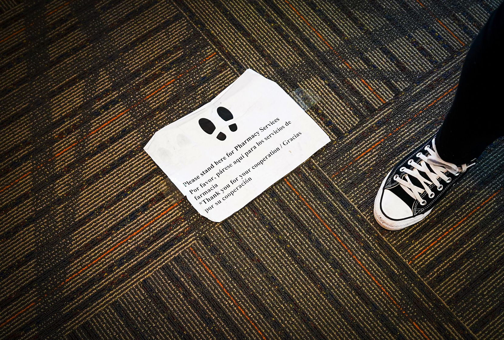 A sign on the floor instructed clients where to wait outside the doorway to fill prescriptions at St. Vincent de Paul Pharmacy at the Northwest Community Center on April 3, 2020, in Dallas. The pharmacy doubled its prescription volume as the coronavirus spread in Dallas County.