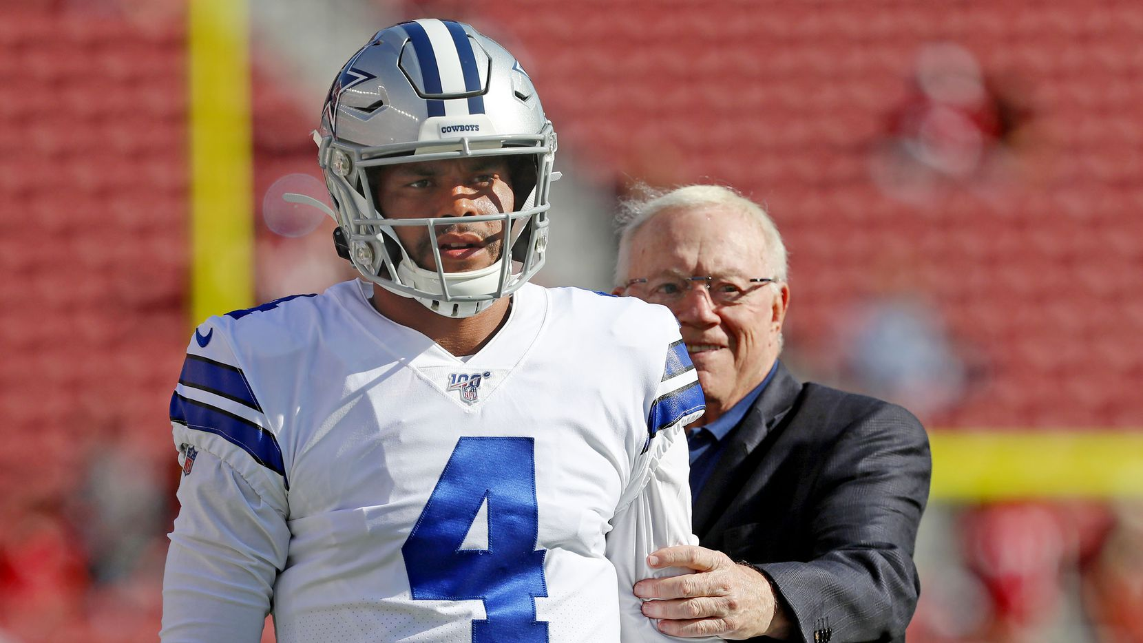 Dallas Cowboys owner Jerry Jones, right, stands behind quarterback Dak Prescott (4) as player warm up before an NFL preseason football game against the San Francisco 49ers in Santa Clara, Calif., Saturday, Aug. 10, 2019.