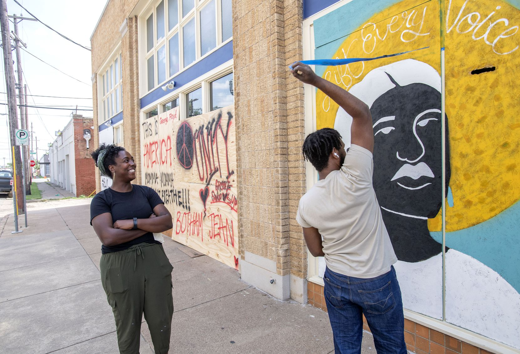 Desiree Vaniecia (left) watches as Joeneal Berry pulls masking tape off of a mural they painted on plywood on Monday, June 1, 2020 in Deep Ellum in Dallas.