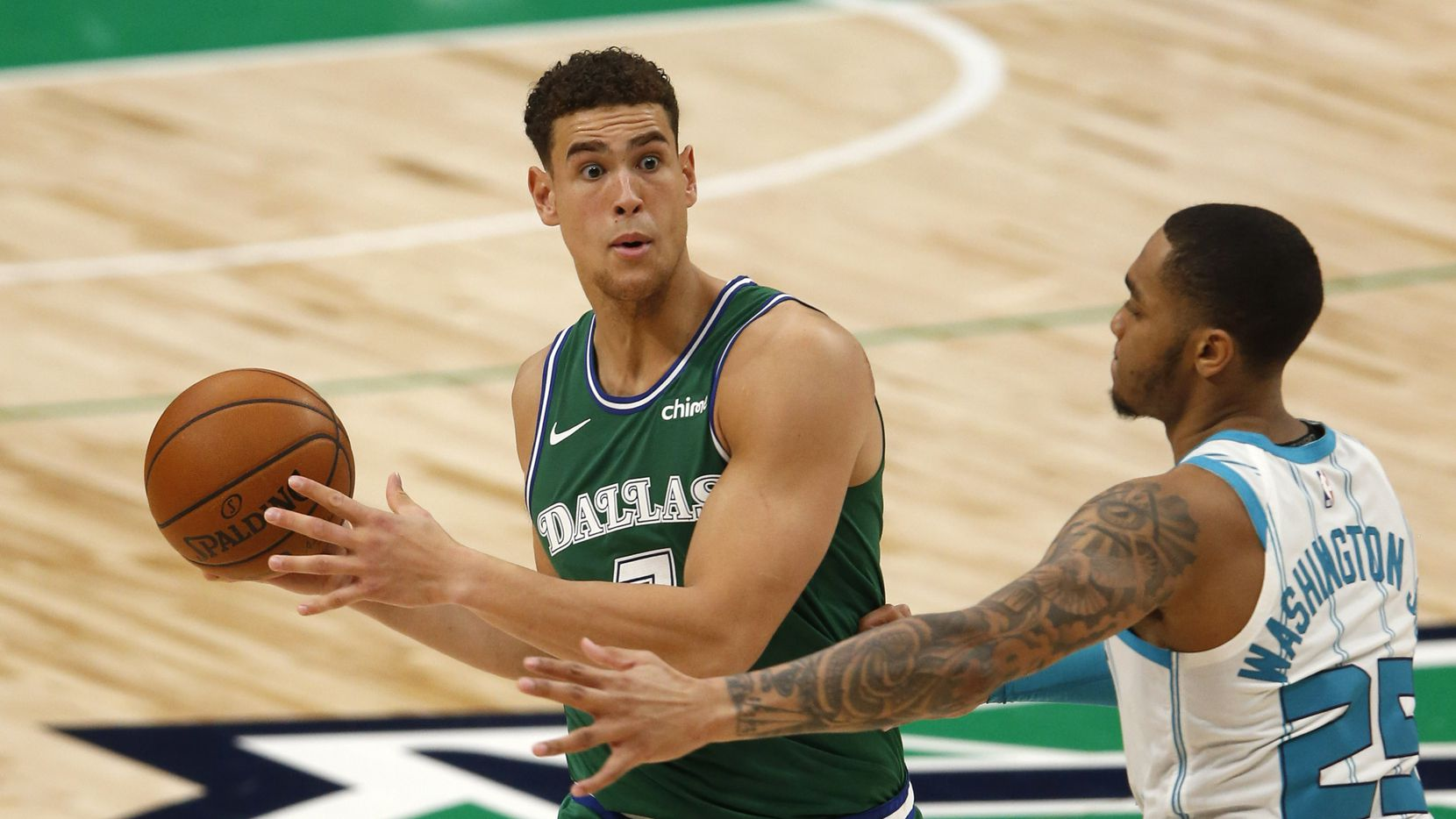 Dallas Mavericks center Dwight Powell (7) looks to pass as he is defended by Charlotte Hornets forward P.J. Washington (25) during the second quarter of play in the home opener at American Airlines Center on Wednesday, December 30, 2020 in Dallas.