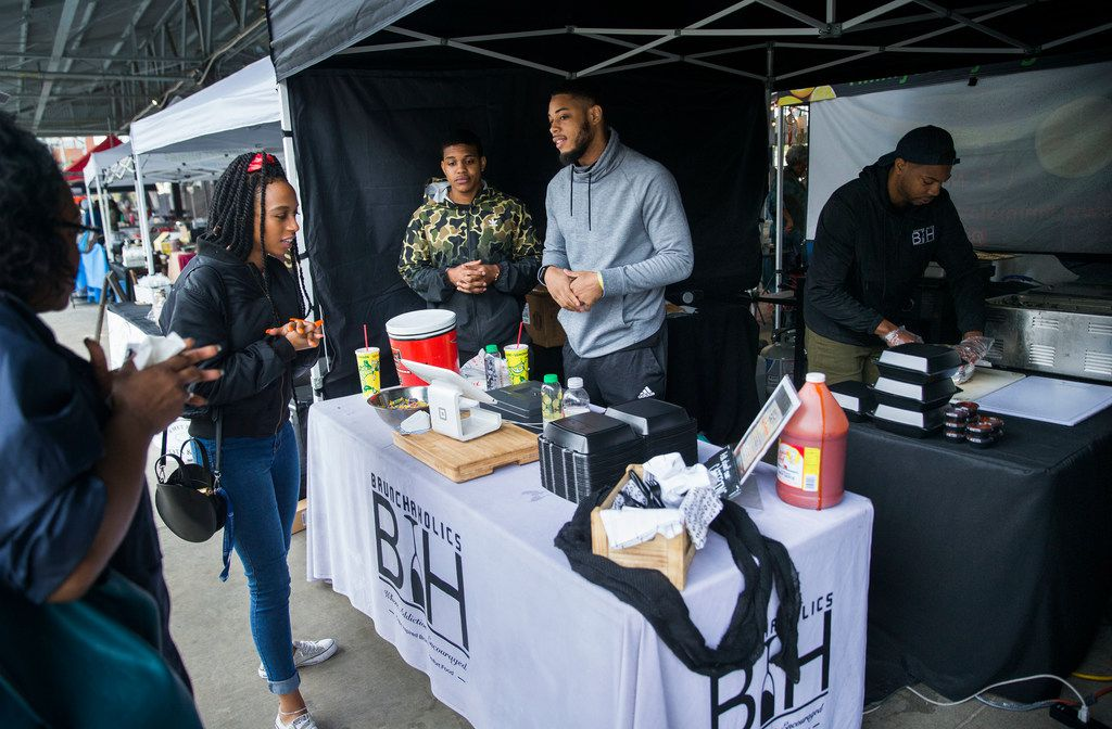 "Jherron Sutton of Dallas, left,  orders a plate to go from Cornelius Malik Washington, camouflage jacket, and Simeon Brinkley, second right, while Jessie Washington, Brunchaholics owner and chef, wraps a ""Soul Food Burrito""  his company's booth at the Dallas Farmers Market in Dallas on Saturday, March 30, 2019. Jessie said he changes the menu each weekends, and he'll sell the burritos again in two weeks. (Daniel Carde/The Dallas Morning News)"
