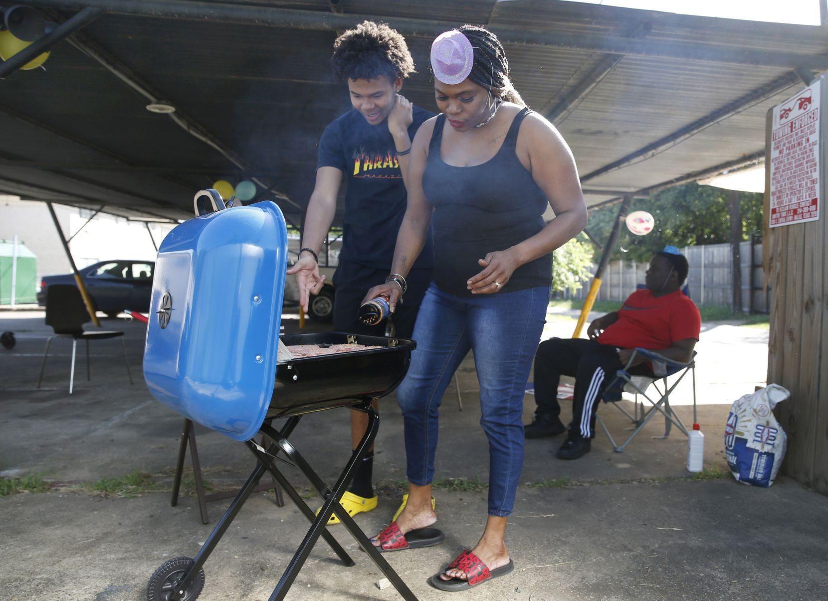 Staceanne Sykes (right) and her son Kenneth Sykes, 16, tend to burgers on the grill as Kenneth's friend Tyren Briggs, 16, sits in the background during a birthday celebration for her youngest son Kaden, 11, at her apartment building's parking lot in Dallas.  Sykes was driving for Postmates and Instacart but stopped because she didn't want to take the risk of bringing home the coronavirus. As a disabled veteran, she gets a monthly stipend, but it doesn't pay for everything.