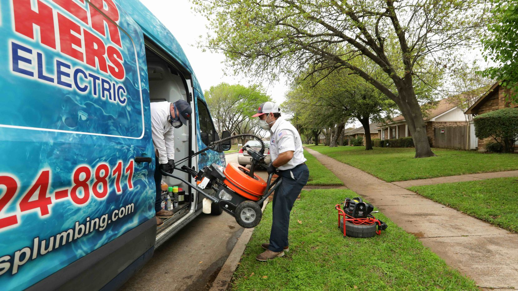 Garrett Bullard, left, and Dylan Ervin, with Baker Brothers, load the van after completing work on a customer's septic line at a house in Garland on Monday.