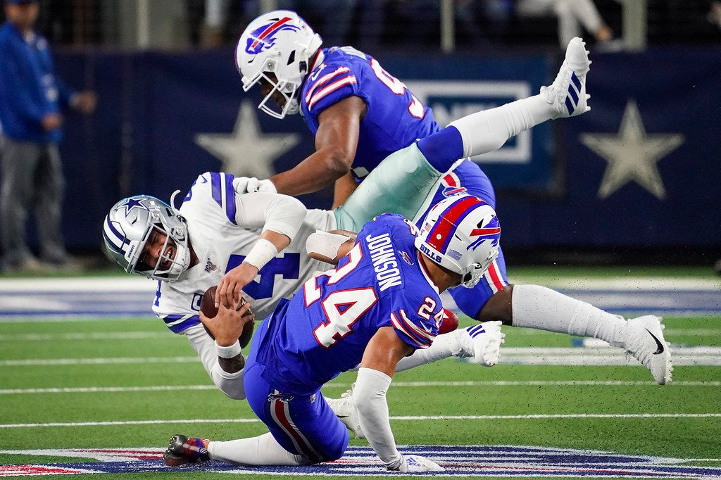 Dallas Cowboys quarterback Dak Prescott (4) is knocked off his feet by Buffalo Bills cornerback Taron Johnson (24) and defensive tackle Ed Oliver (91) during the second half of an NFL football game at AT&T Stadium on Thursday, Nov. 28, 2019, in Arlington. (Smiley N. Pool/The Dallas Morning News)