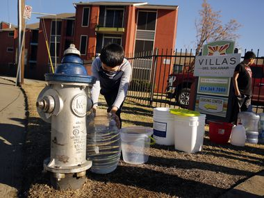 Ivan Garcia, a young resident of the Villas Del Solamar Apartments, fills his water bucket from a fire hydrant on Park Lane in Dallas, Monday, February 22, 2021. The residents of the Vickery Meadow apartment complex say they've been without water for a week now following the winter storm.