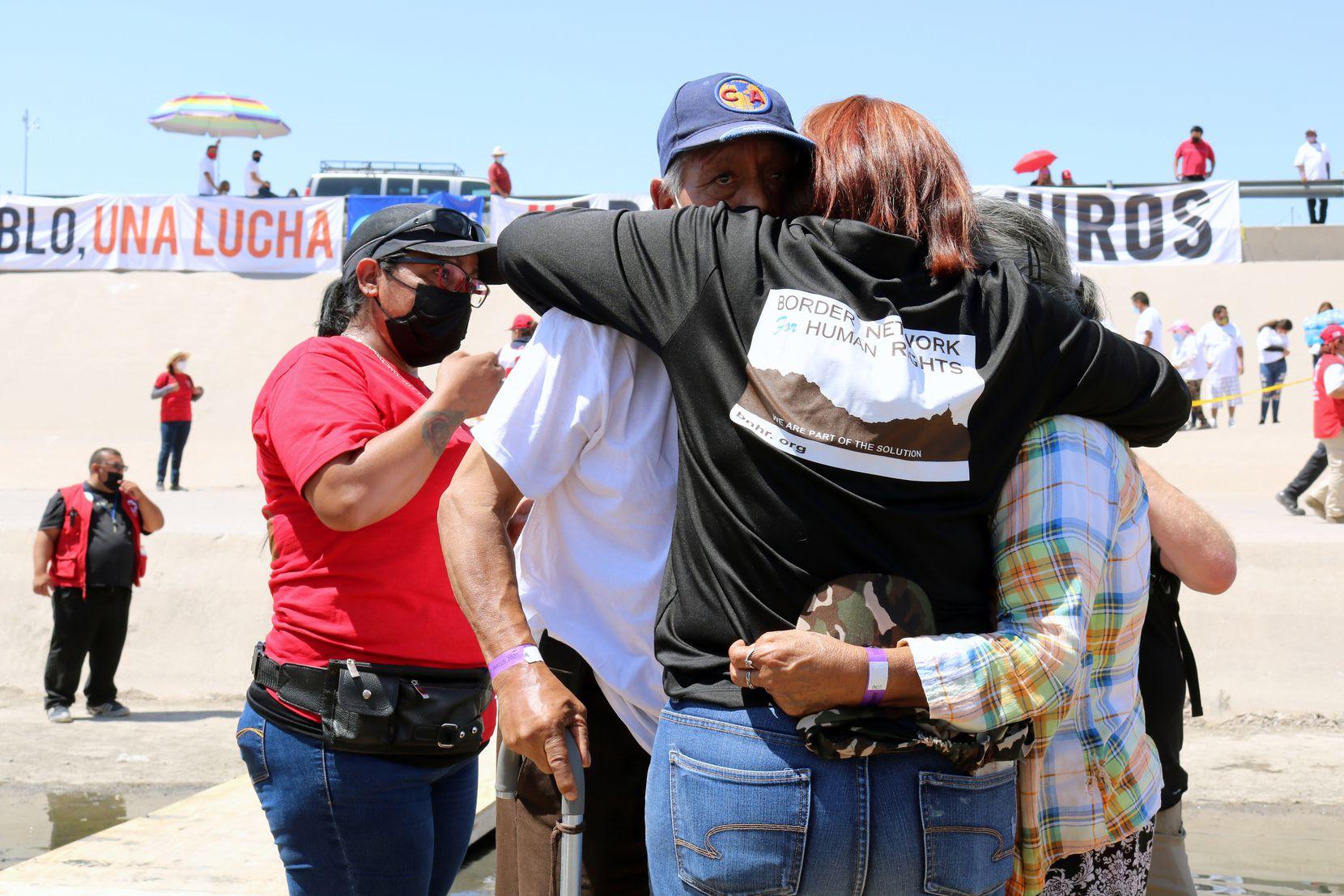 """María Cecilia """"Ceci"""" Rueda, de 41 años, abraza a su padre José de 76 años y a otra persona no identificada durante el evento """"Abrazos no Muros"""" en el Río Grande que divide El Paso de Ciudad Juárez, el sábado 19 de junio de 2021."""