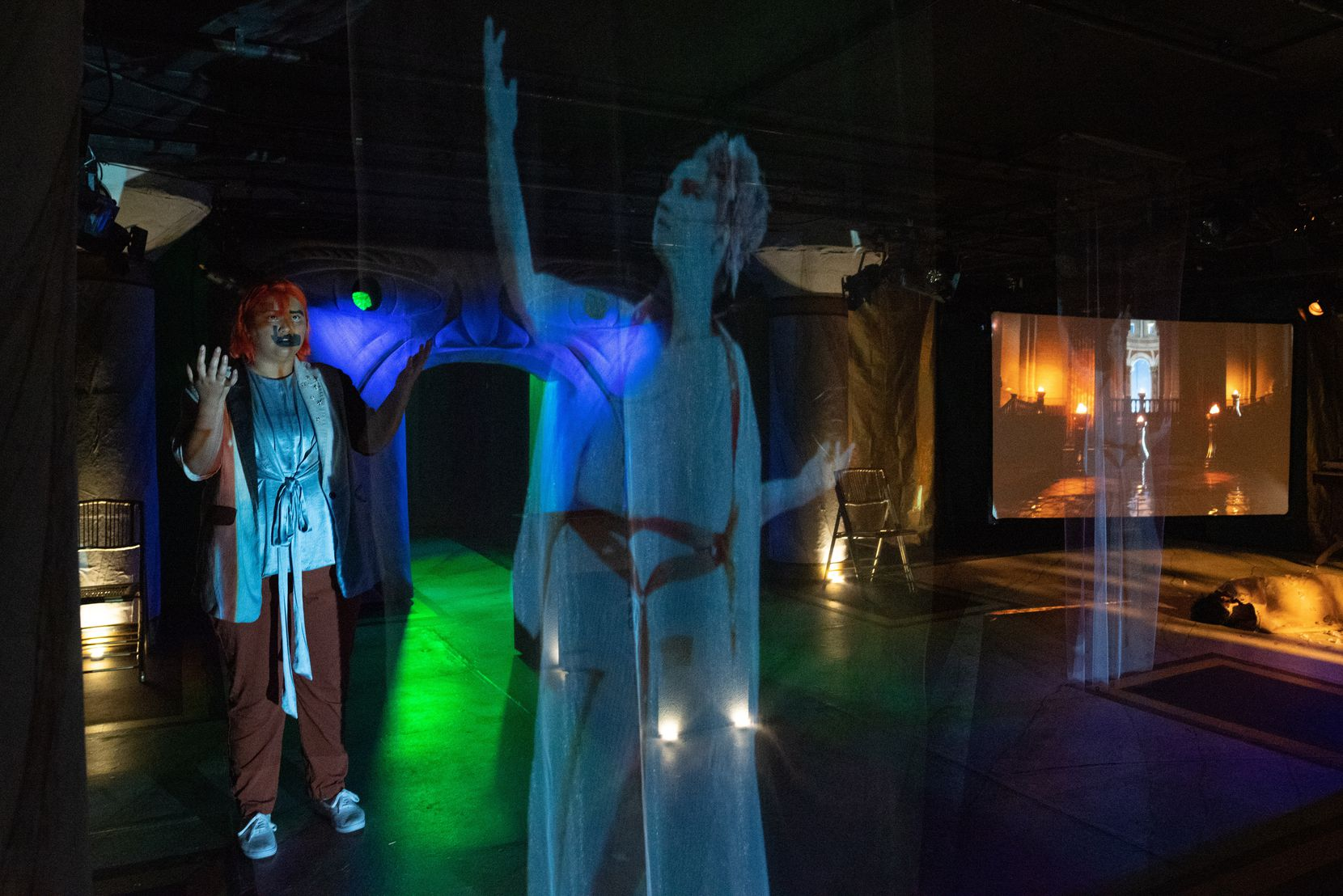 """Mindamora Rocha (left) as Ismene and a projected Anastasia Muñoz as Iereia in """"Stronger Than Arms,"""" a new play produced by the Danielle Georgiou Dance Group and presented by Undermain Theatre in its Deep Ellum basement space."""
