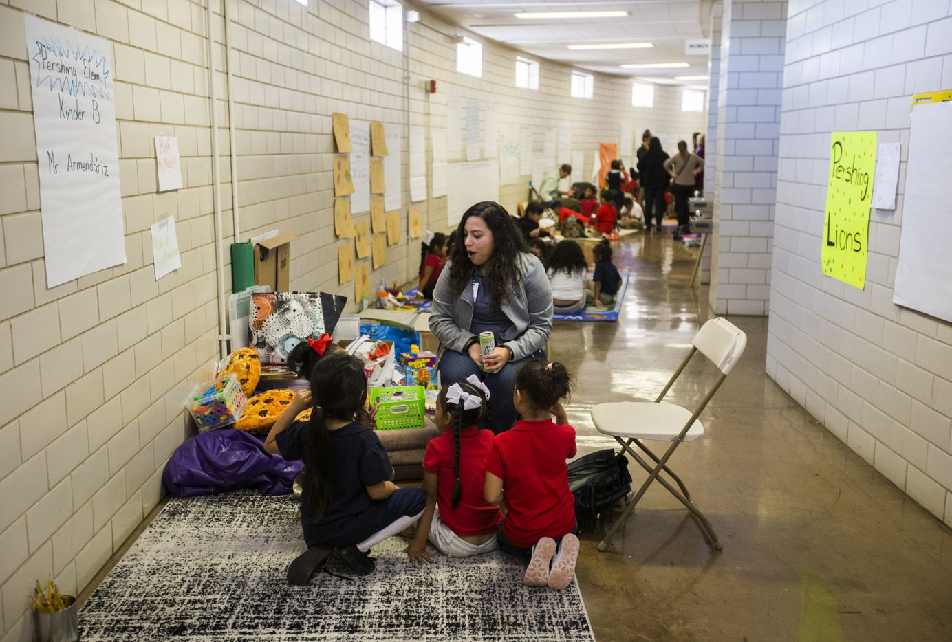 Instructional Specialist Tania Fuentes helps with a Pershing Elementary School kindergarten class in the hallway at Alfred J. Loos Athletic Complex on Wednesday, October 23, 2019 in Dallas. Pershing, Burnet and Cigarroa Elementary schools were damaged as multiple tornadoes ripped through the DFW area on Sunday night. (Ashley Landis/The Dallas Morning News)