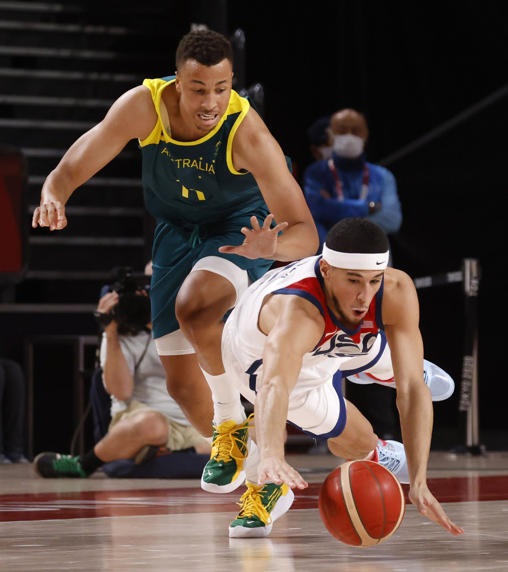 USA's Devin Booker (15) dives for a loose ball as Australia's Dante Exum (11) follows during the first half of a men's basketball semifinal at the postponed 2020 Tokyo Olympics at Saitama Super Arena, on Thursday, August 5, 2021, in Saitama, Japan. USA defeated Australia 97-78 to advance to the gold medal game. (Vernon Bryant/The Dallas Morning News)