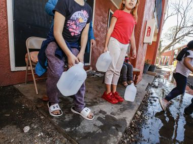 Alina Mendoza, 6, and Deveany Mendoza, 10, carry jugs of water into their apartment at the Villas de Solamar apartments in Dallas, on Wednesday. The apartments' water lines froze and broke in the severe cold last week, leaving residents without running water. In Irving, similar scenes unfolded as many apartment dwellers were left without water.