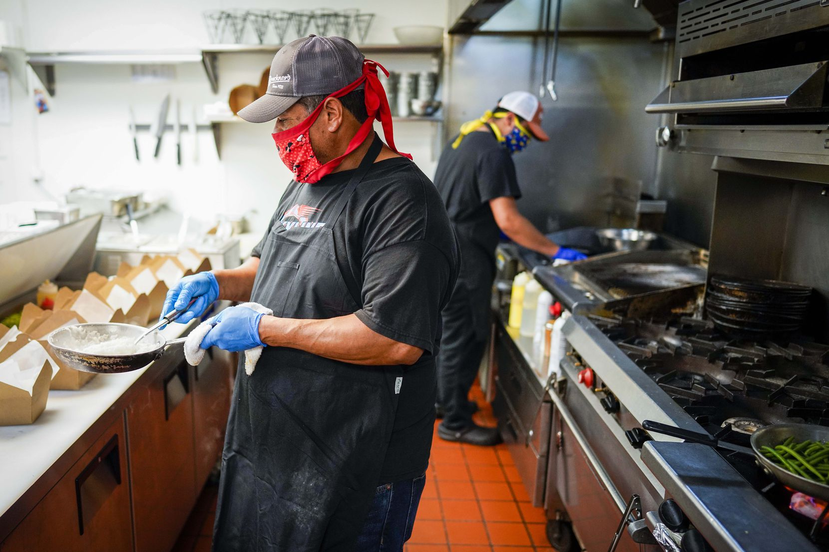 Cruz Garcia (front) and Eduardo Garcia wear face masks as they work in the kitchen at TJ's Seafood restaurant on Tuesday in Dallas. The restaurant has partnered with a testing company to test all of their employees for COVID-19, screen and train them. (Smiley N. Pool/The Dallas Morning News)