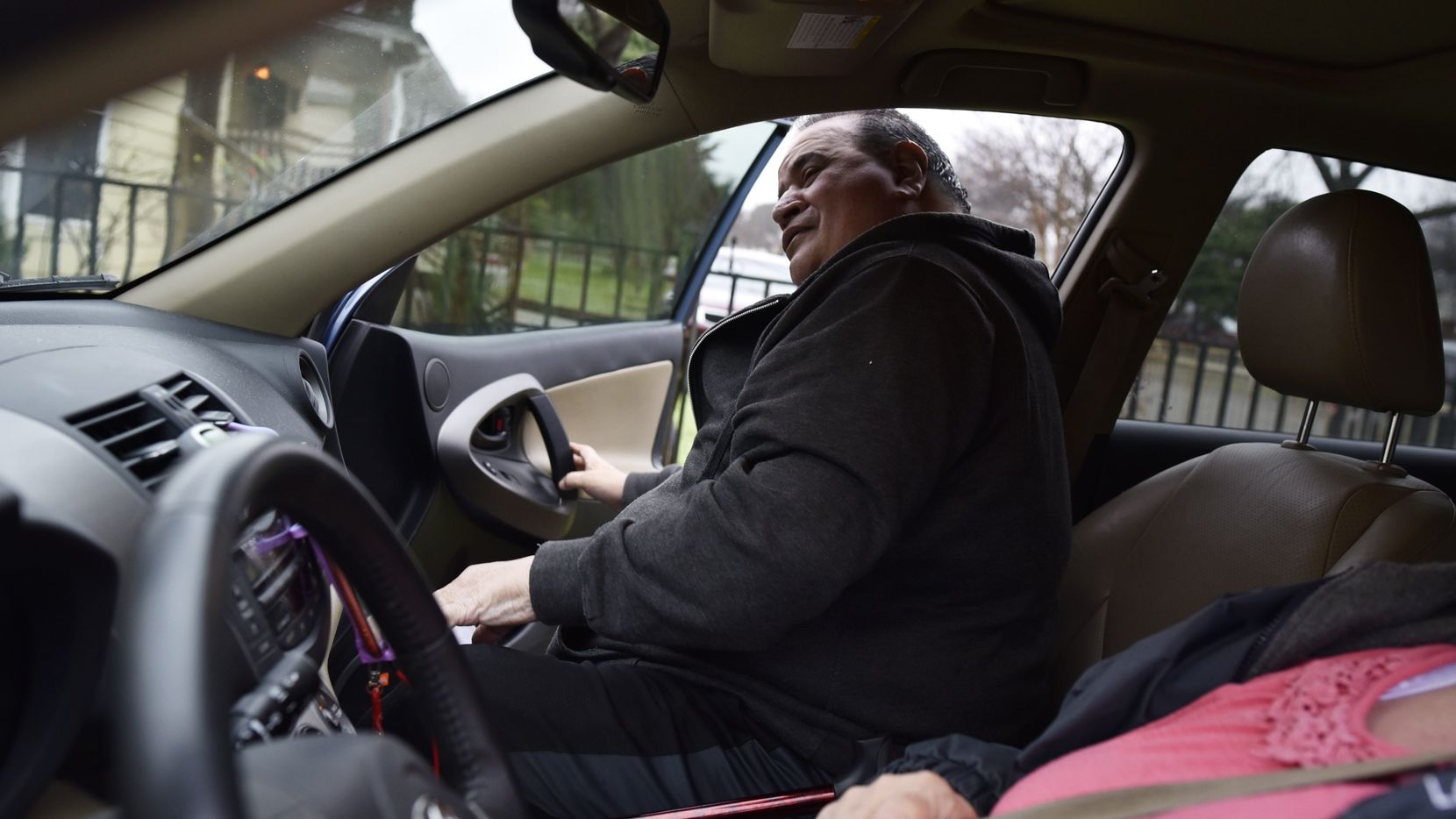 Steven Valdez, 64, enters Julia Gibson's car for his ride to a doctor's appointment. The Dallas resident, who can't walk because of a foot condition, hopes to see more transportation services for people like him.