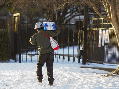A man walks home with a case of drinking water distributed at the Literacy Achieves nonprofit in Vickery Meadow to nearby residents living without water after a winter storm brought snow and continued freezing temperatures to North Texas on Feb. 18.
