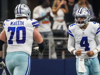 Dallas Cowboys quarterback Dak Prescott (4) celebrates with offensive guard Zack Martin (70) after throwing a touchdown pass to wide receiver Amari Cooper during the third quarter of an NFL football game against the Carolina Panthers at AT&T Stadium on Sunday, Oct. 3, 2021, in Arlington. (Smiley N. Pool/The Dallas Morning News)
