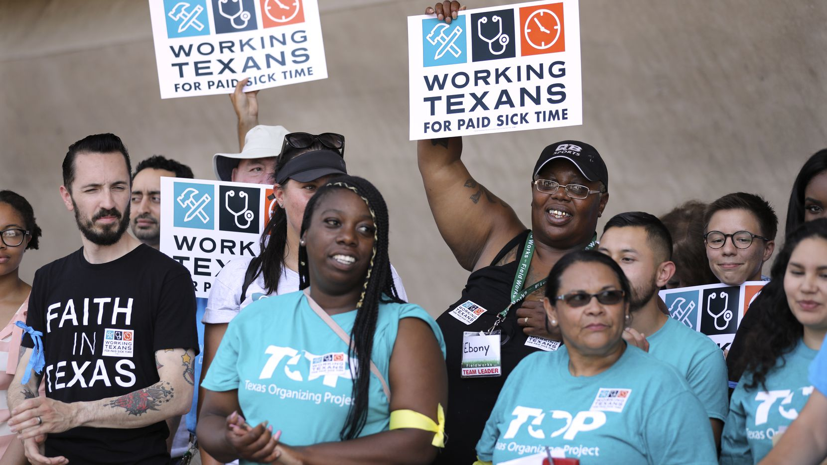 Supporters of a petition drive hold signs during a news conference before a coalition of labor and faith groups and political activists delivered petitions at Dallas City Hall calling for an ordinance mandating paid sick time to be placed on the November ballot June 11, 2018.