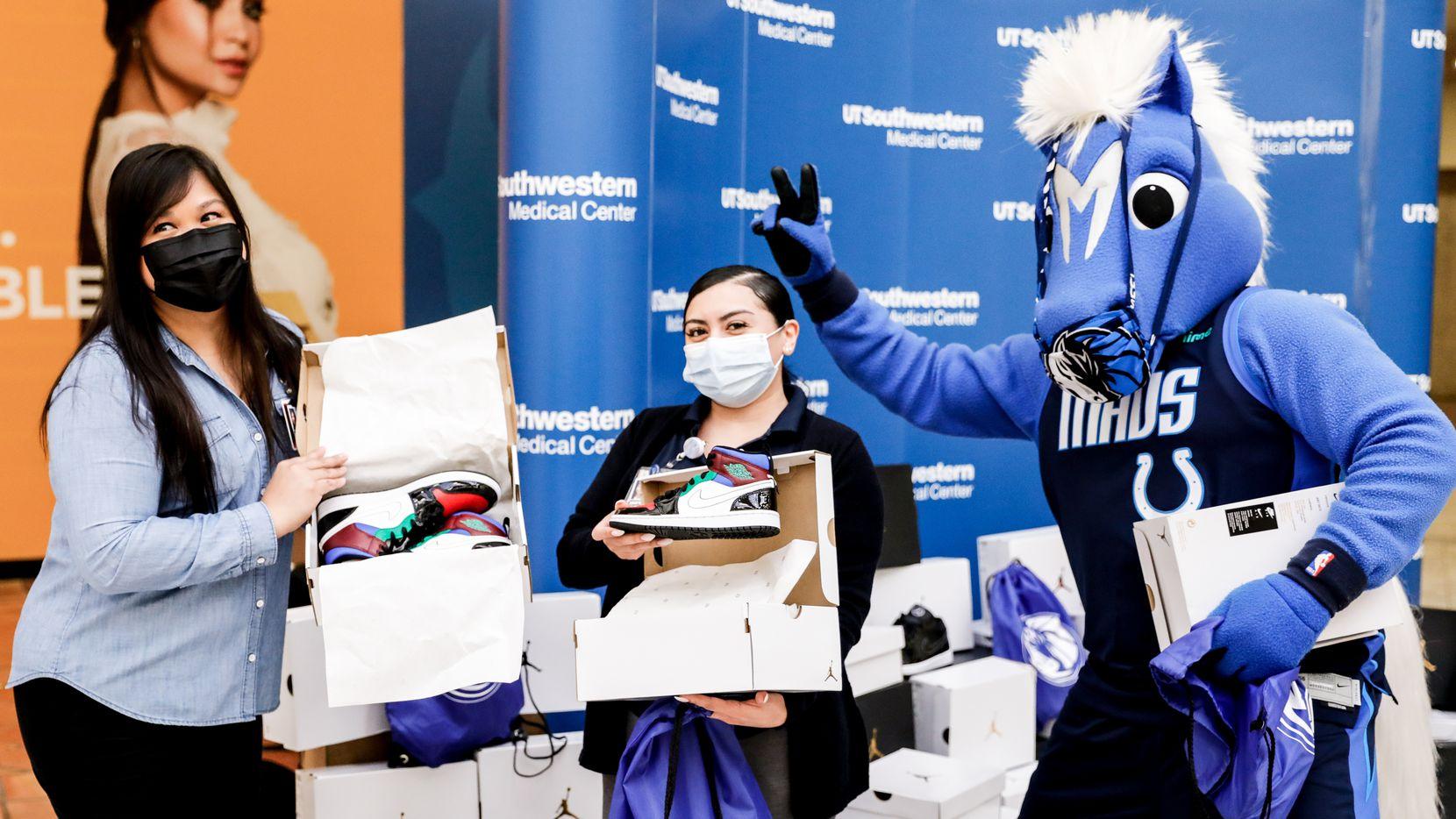 La mascota de los Mavericks de Dallas posa con trabajadores UT Southwestern que recibieron la donación de Luka Doncic.