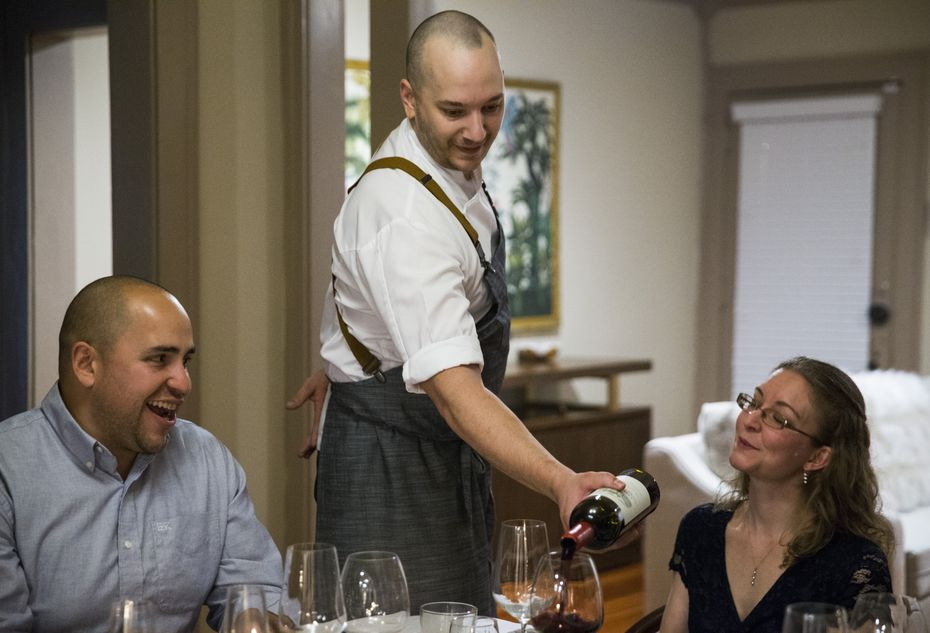 Chef Casey La Rue pours wine for guests Eric Carlos and Ann Davis at a pop-up dinner in Dallas.