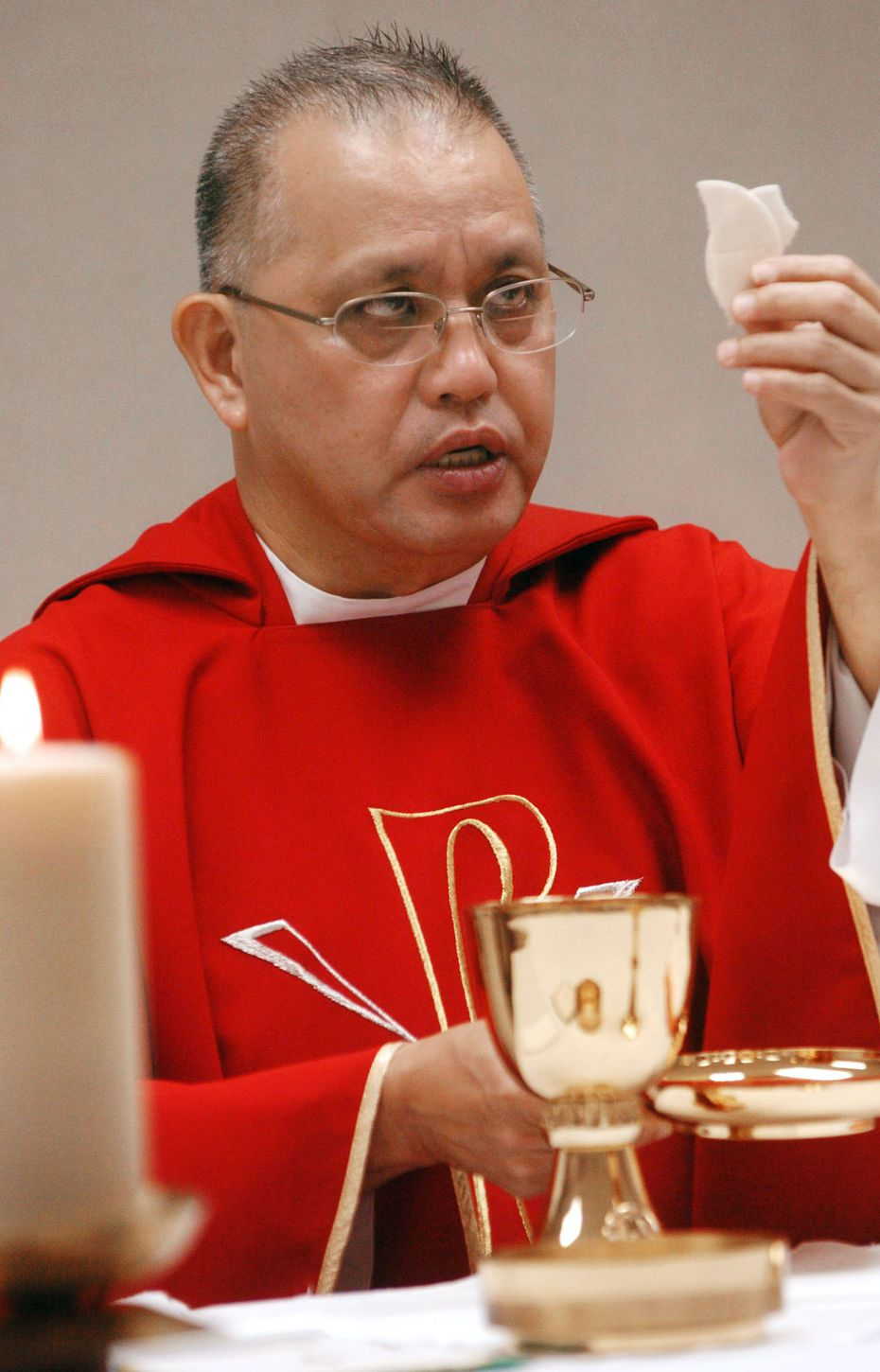 Rev. Edmundo Paredes prepares for communion during a mass in June, 2008 at St. Cecilia Catholic church, after fire destroyed the sanctuary.