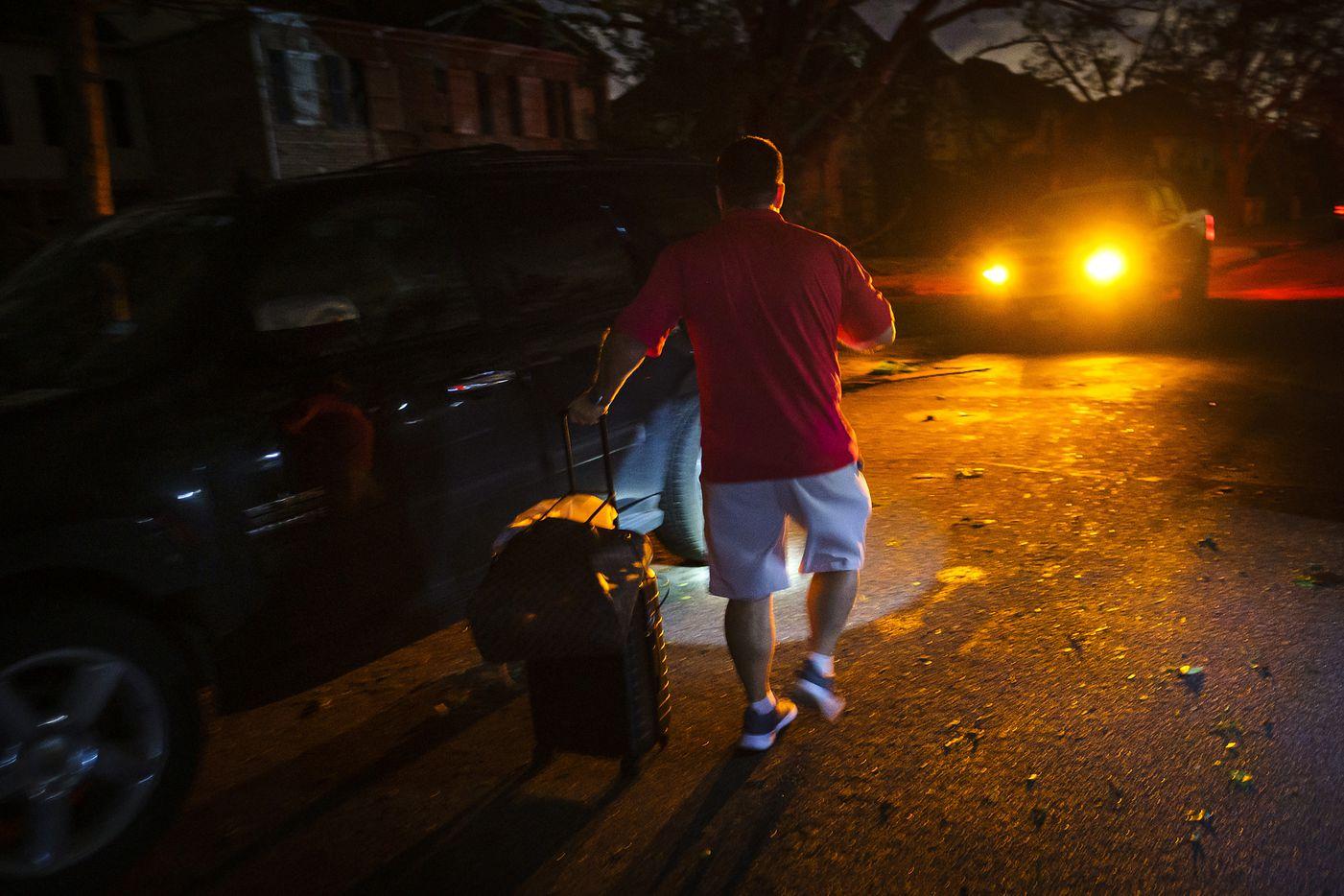 A resident takes a suitcase to his car in a darkened neighborhood near the intersection of Royal and Hillcrest that was damaged by a tornado on Sunday, Oct. 20, 2019, in Dallas.