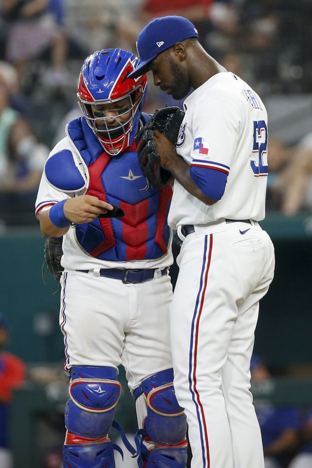 Texas Rangers relief pitcher Taylor Hearn (52) meets with Texas Rangers catcher Jose Trevino (23) on the mound during the sixth inning against the Los Angeles Angels at Globe Life Field on Thursday, Aug. 5, 2021, in Arlington. (Elias Valverde II/The Dallas Morning News)