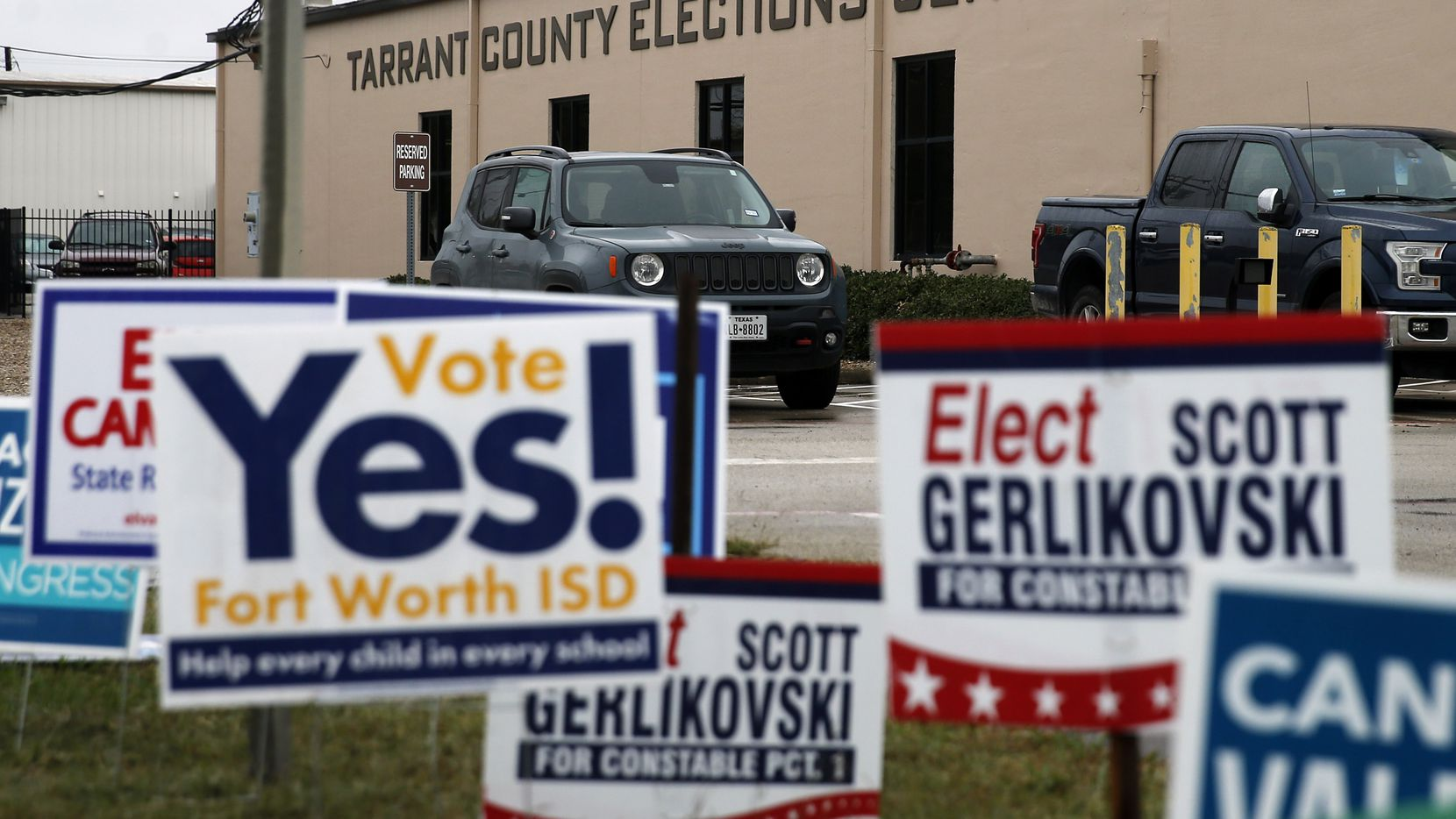 Campaign signs line the street outside the Tarrant County Elections Center in Fort Worth, Tuesday, October 27, 2020.