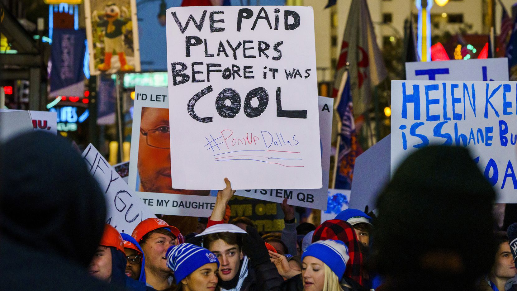 A fan holds up a sign reading ÒWe Paid Players Before it was Cool,Ó during ESPN College GameDay before an NCAA football game between Memphis and SMU on Saturday, Nov. 2, 2019, in Memphis, Tenn.