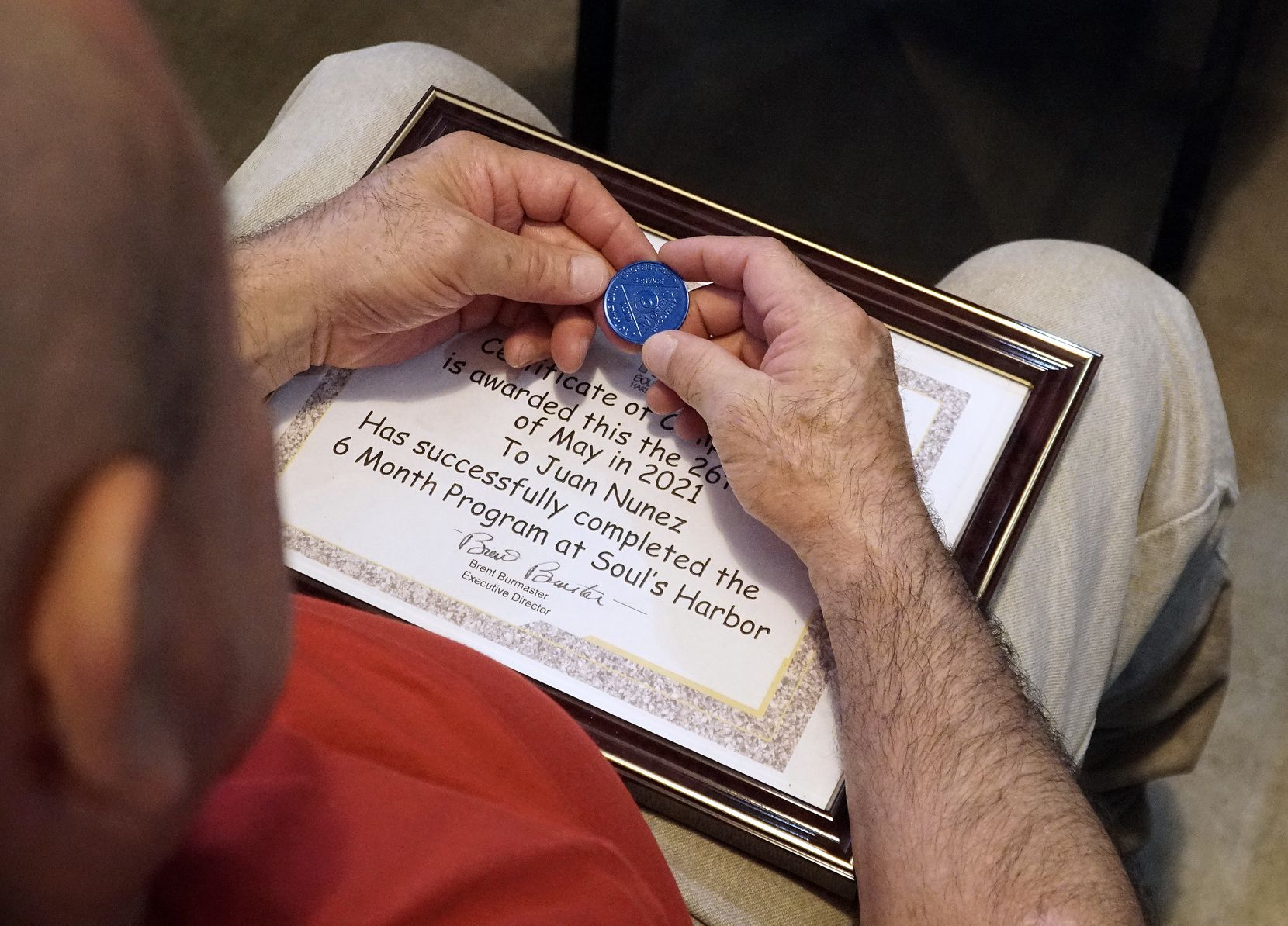 Juan Nunez holds his six-month sobriety chip at Soul's Harbor.