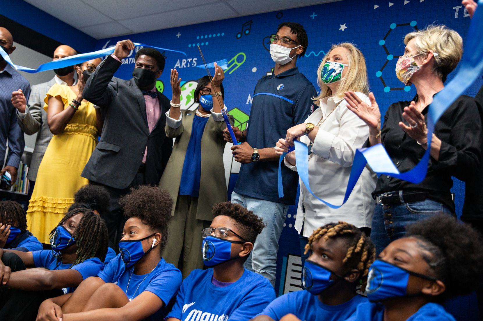 Dallas Mavericks guard Nate Hinton cuts the ribbon at the Mavs Foundation's unveiling of its newest reading and learning center renovation at the Moorland YMCA at Oak Cliff on August 3, 2021. (Shelby Tauber / Special Contributor)
