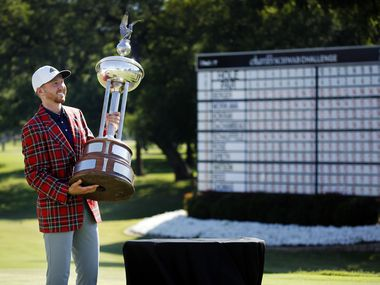 On the 18th green, PGA Tour golfer Daniel Berger poses with in the Leonard Trophy after defeating Collin Morikawa in a one hole playoff in the final round of the Charles Schwab Challenge at the Colonial Country Club in Fort Worth, Sunday, June 14, 2020. The Challenge is the first tour event since the COVID-19 pandemic began.