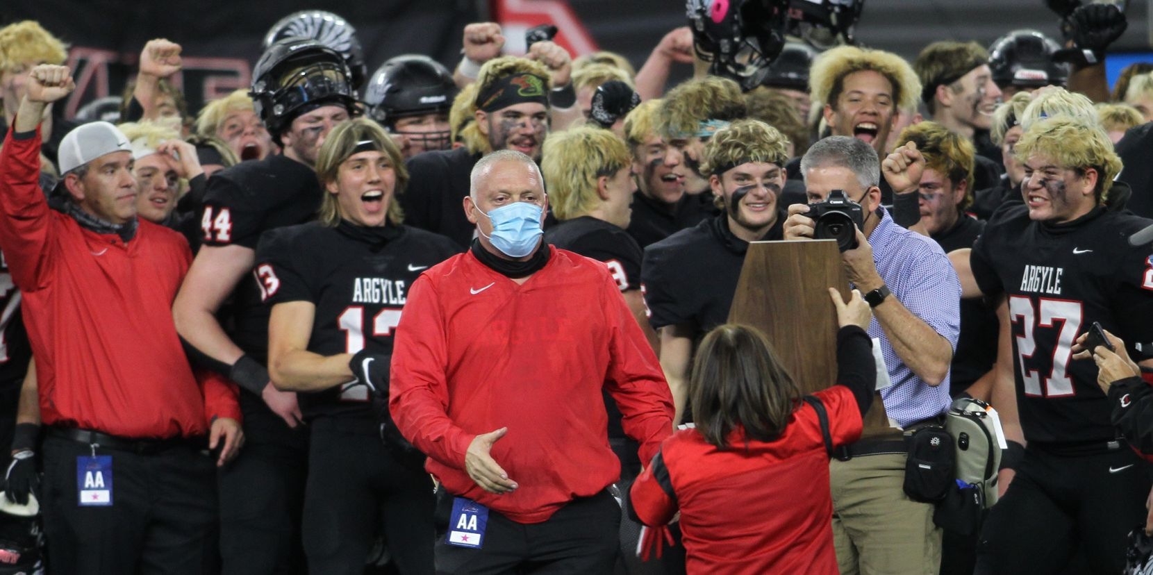 Argyle head coach Todd Rodgers steps up to accept the state championship trophy as his players react following their 49-21 victory over Lindale. The two teams played their Class 4A Division l state championship football game at AT&T Stadium in Arlington on December 18, 2020.
