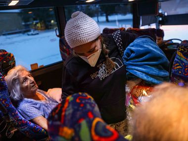 Marleny Almendarez, 38, makes her way into the bus that serves as a warming center located in Pleasant Oaks Recreation Center for the second consecutive night in Dallas on Wednesday, Feb. 18, 2021. Almendarez's house had inconsistent electricity to keep her home warm after a snow storm hit Texas.