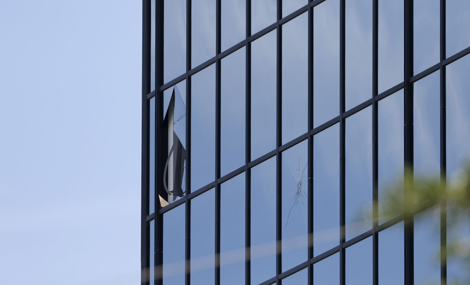 Bullet holes are seen near a broken window at the office building. (Jae S. Lee/Staff Photographer)