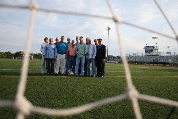 J.J. Pearce High School alumni, who graduated in the mid- to late-1970s, gather on the school's soccer field on May 1. After their friend and fellow teammate, Rob Harper, died in January, members of the group began efforts to establish an award and memorial fund in his honor.