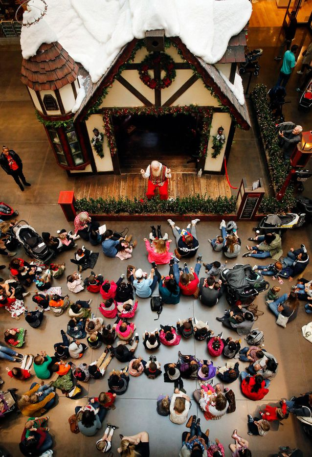 Santa Claus visits with kids outside his cottage at NorthPark Center in Dallas on Dec. 13, 2018. For the past 30 years, Carl Anderson has portrayed Santa at NorthPark. He has story time for children before sitting and listening to their Christmas wishes.