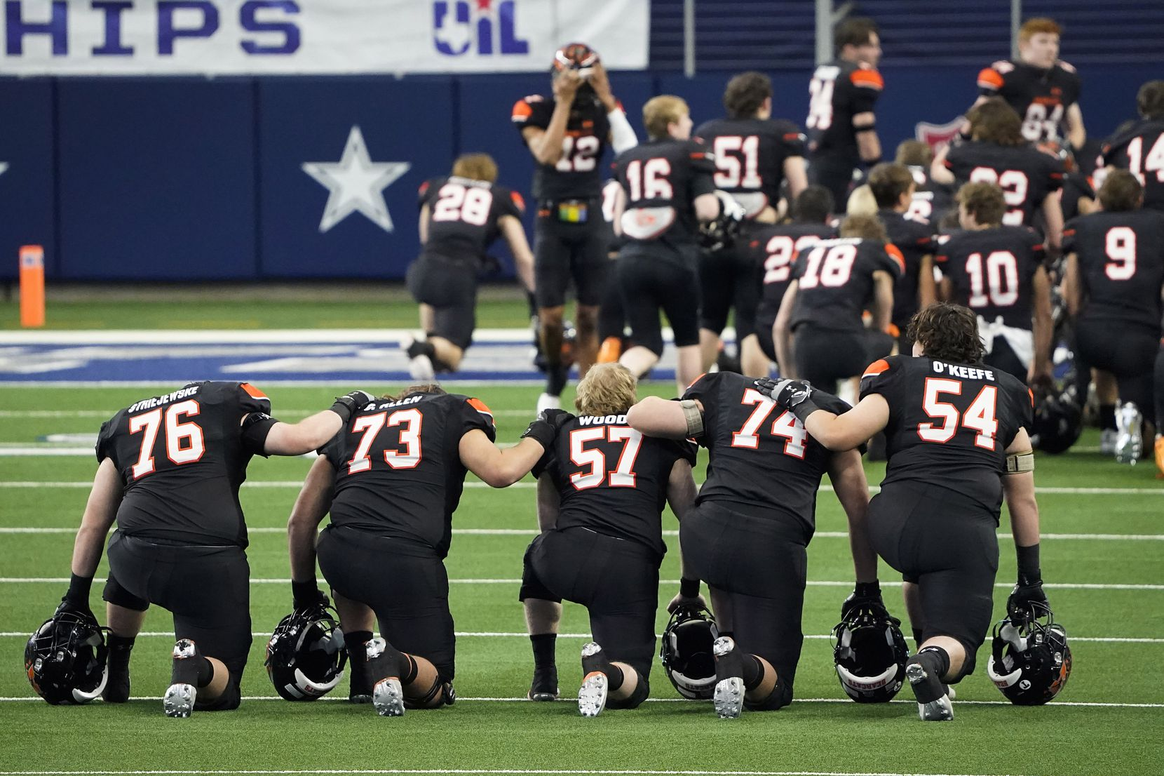 Aledo players kneel in prayer before the first half of the Class 5A Division II state football championship game against Crosby at AT&T Stadium on Friday, Jan. 15, 2021, in Arlington. (Smiley N. Pool/The Dallas Morning News)