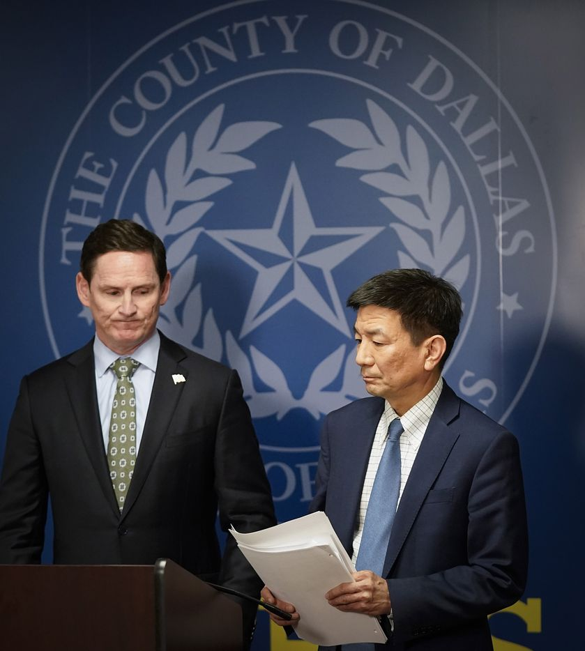 Dallas County Judge Clay Jenkins turns the podium over to Dr. Philip Huang, Director of Dallas County Health and Human Services, after announcing that a local state of disaster for public health emergency has been declared in the county, due to more cases of the new coronavirus, late Thursday, March 12. 2020, in Dallas.