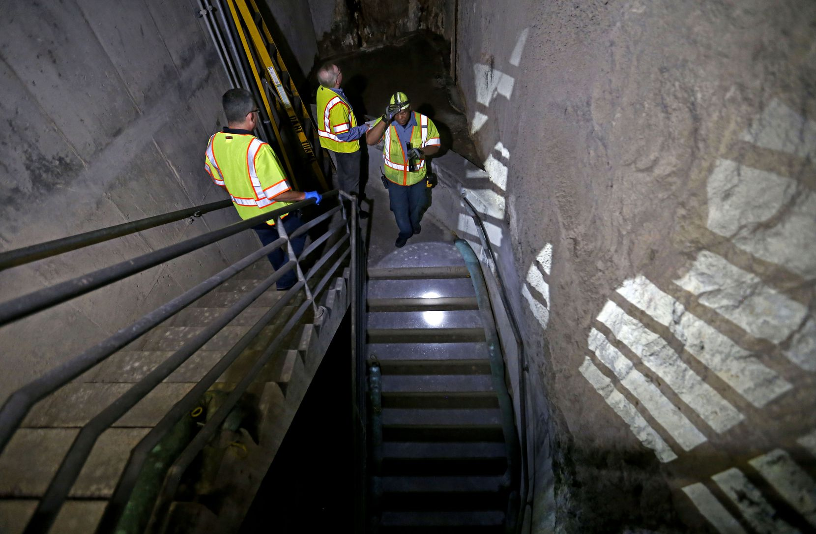 Mechanic Bill Lakes (right) leads the way, followed by DMN real estate editor Steve Brown and Javier Molina, DART's interim technical administrator, down several flights of stairs to the unfinished Knox Street light rail station 80 feet below North Central Expressway.