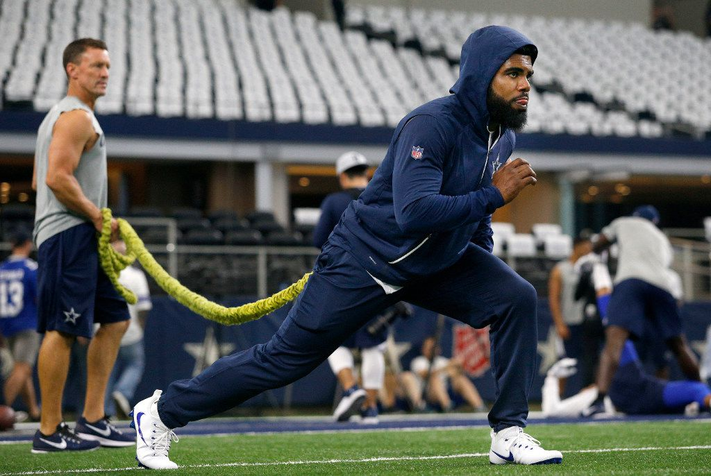 Dallas Cowboys running back Ezekiel Elliott stretches with the help of trainer Britt Brown during pregame warmups before the New York Giants game at AT&T Stadium in Arlington, Texas, Sunday, September 10, 2017. (Tom Fox/The Dallas Morning News)