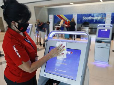 Southwest Airlines employee Jeanne Ryan wipes down a kiosk at Dallas Love Field. For the many customers who haven't used tickets because of the pandemic, Southwest is offering to convert their travel funds to points that never expire.