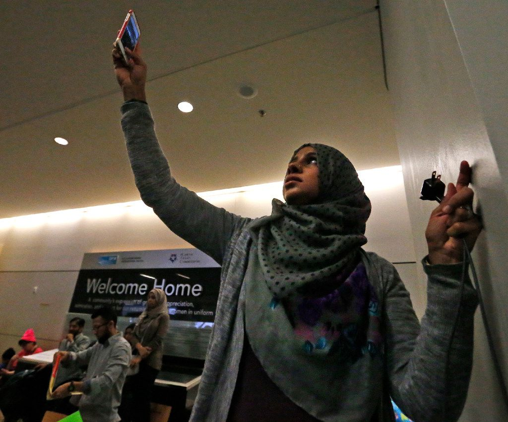 Samina Mohammad takes a phone video of the protesters at the international arrivals gate in Terminal D at DFW Airport on Sunday, January 29, 2017. (Louis DeLuca/The Dallas Morning News)