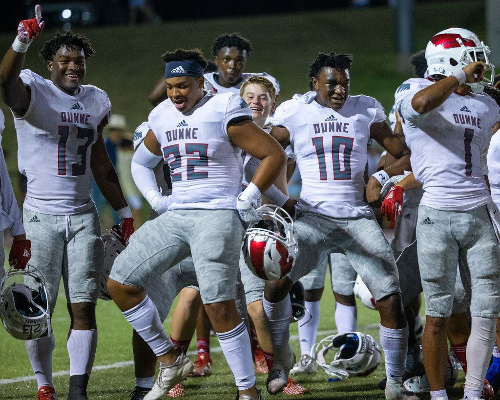Bishop Dunne players, (from left) Josh Emmanuel, Sam Strong, Alex Orji, and Simeon Evans celebrate their win against All Saints' Episcopal School at Young Field McNair Stadium in Fort Worth, Texas, on Friday, Sep. 27, 2019.