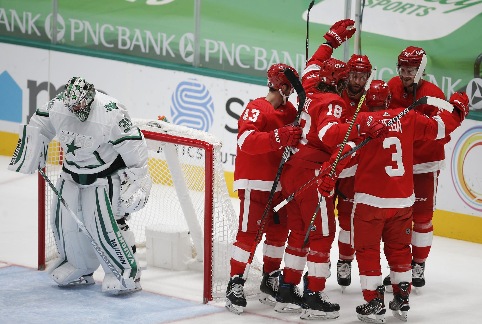 Dallas Stars goaltender Anton Khudobin (35) looks on as Detroit Red Wings forward Luke Glendening, third from left, is congratulated by teammates after scoring a goal during the second period of an NHL hockey game in Dallas, Monday, April 19, 2021. (Brandon Wade/Special Contributor)