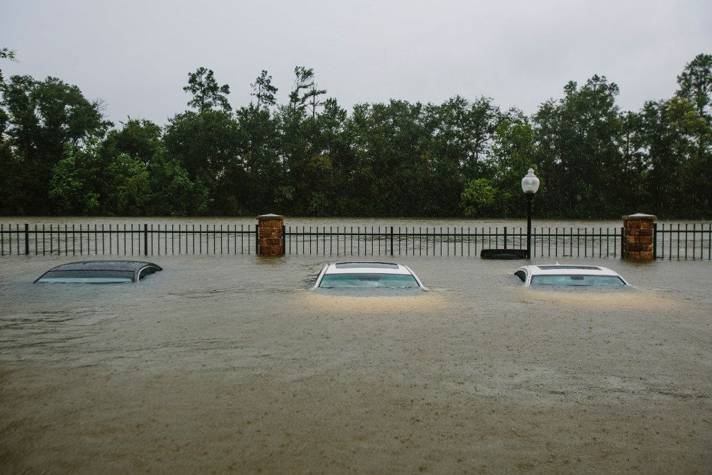 Flooded cars sit in an apartment complex parking lot in Humble on Tuesday.