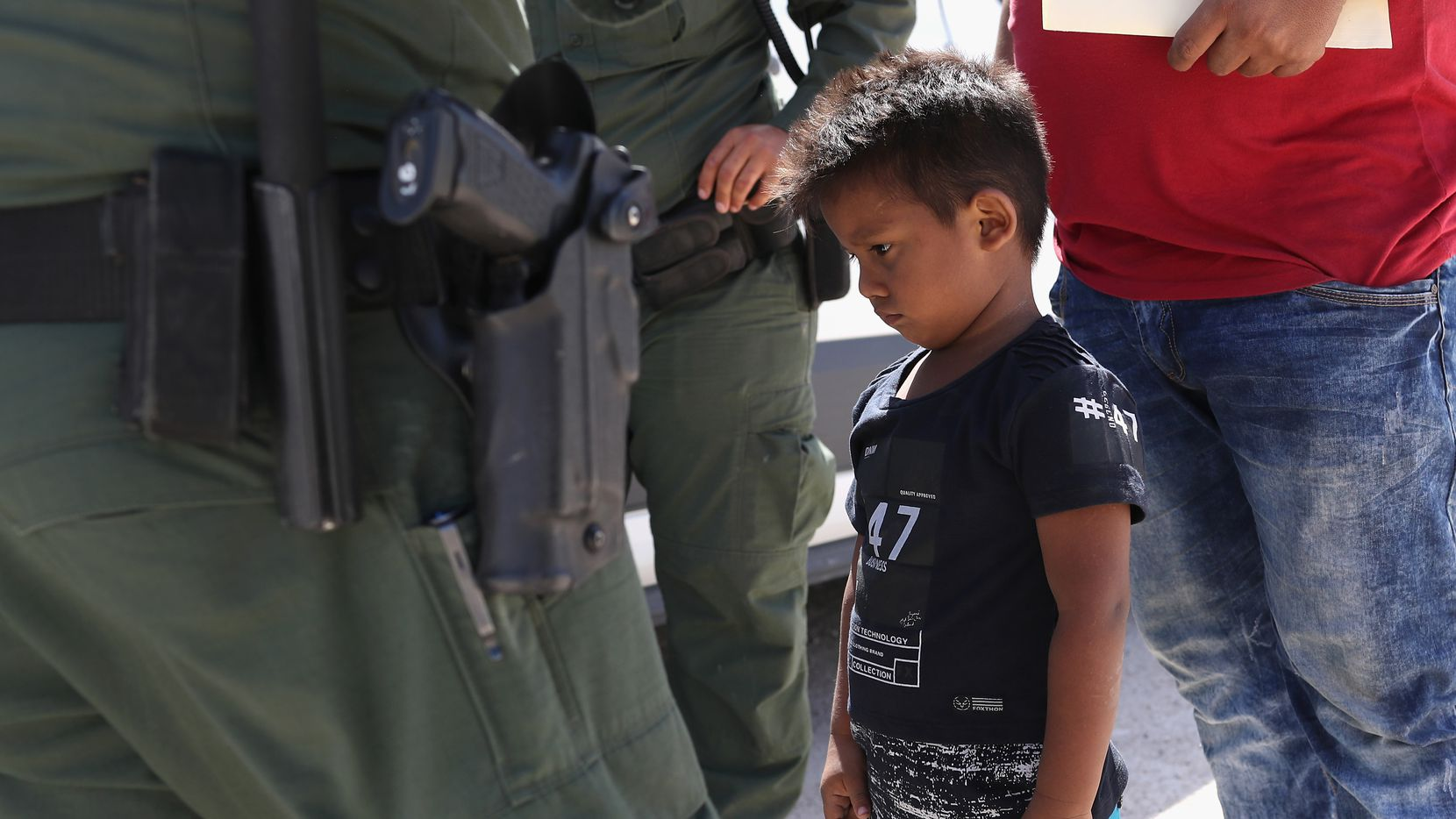 """A boy and father from Honduras are taken into custody by U.S. Border Patrol agents near the U.S.-Mexico Border on June 12, 2018 near Mission, Texas in response to the Trump administration's """"zero tolerance"""" policy. (Photo by John Moore/Getty Images)"""