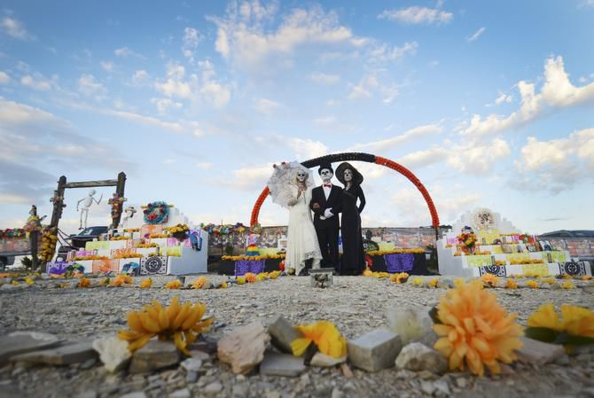 Surrounded by fresh marigolds, participants in the annual Dia De Los Muertos celebration in Terlinga Ghost Town pose between two of the cemetery's altars during the annual Nov. 2 celebration.