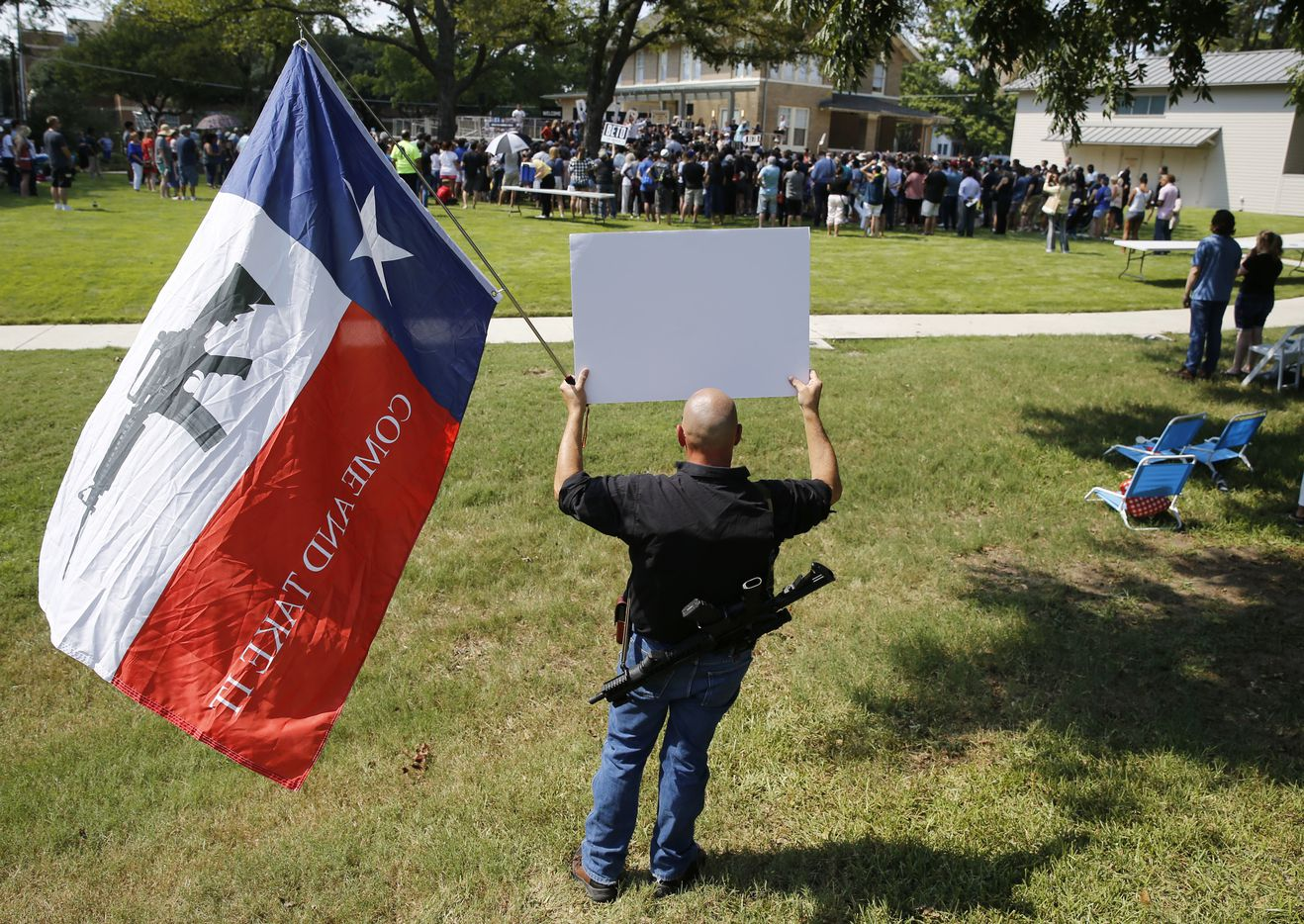 "John Swicegood holds up a sign that reads ""Hell no you will not take my AR-15,"" as Democratic Presidential candidate Beto O'Rourke speaks at a campaign event at Haggard Park in Plano, Texas, on Sunday, September 15, 2019. (Vernon Bryant/The Dallas Morning News)"